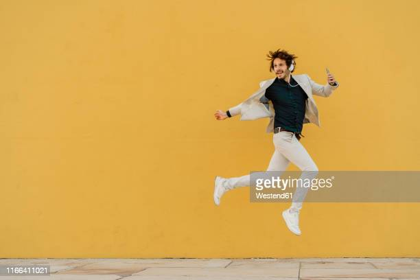 businessman jumping in the air in front of yellow wall listening music with headphones and smartphone - enjoyment ストックフォトと画像