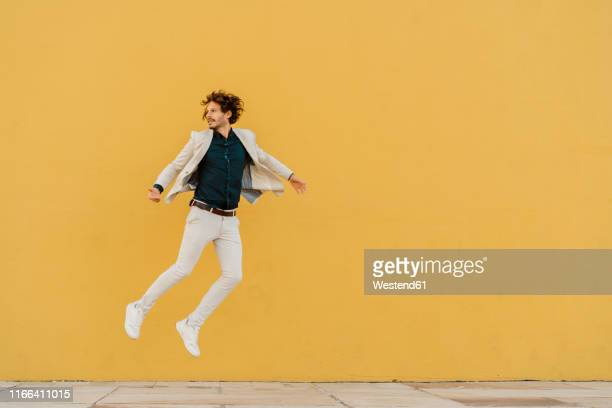 businessman jumping in the air in front of yellow wall - in de lucht zwevend stockfoto's en -beelden