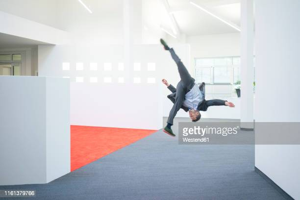businessman jumping mid-air on office floor - acrobatic activity stock pictures, royalty-free photos & images