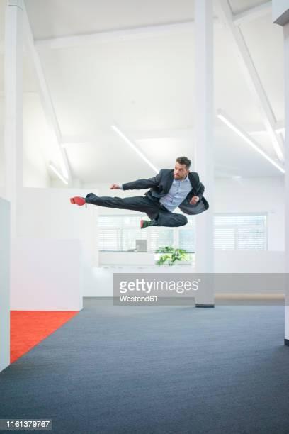 businessman jumping mid-air on office floor - kicking ストックフォトと画像