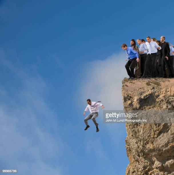 Businessman jumping off cliff while co-workers watch