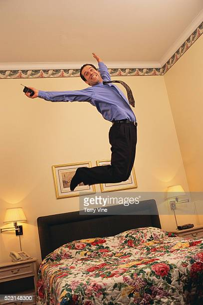 Businessman Jumping on a Bed