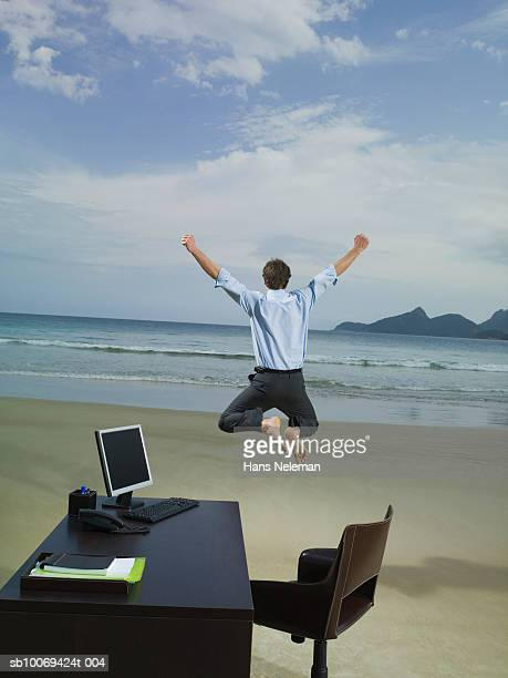Businessman jumping on beach, rear view