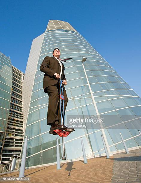 Businessman Jumping on Pogo Stick in Front of Convention Center