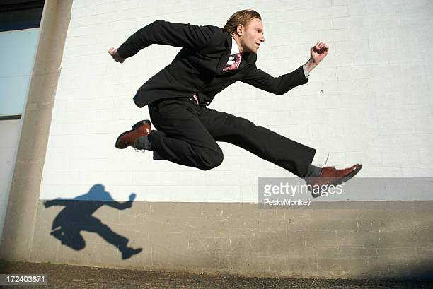 Businessman Jumping Outdoors Against White Wall