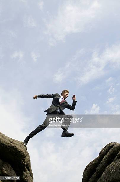 Businessman Jumping Outdoors Over Valley Between Rocks