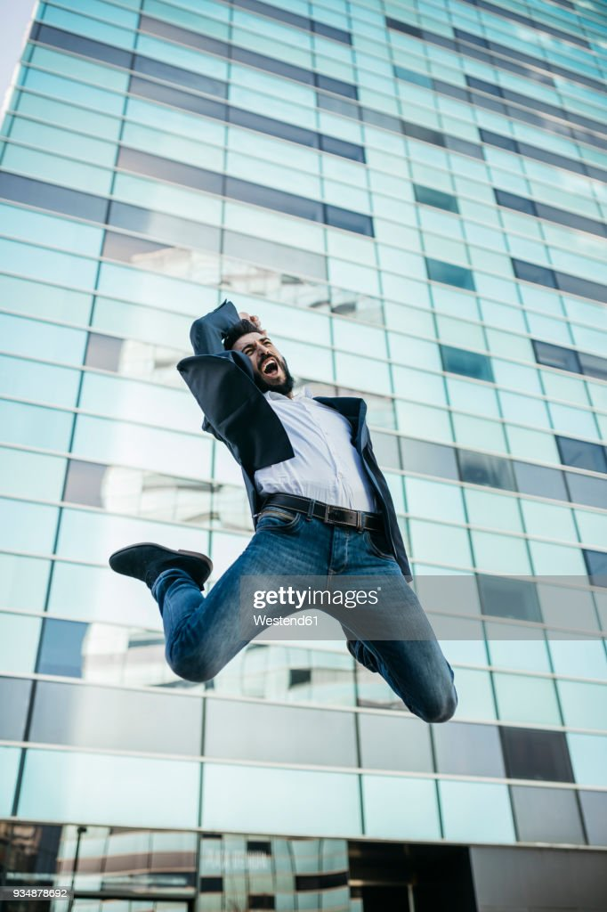 businessman jumping outside office building ストックフォト getty
