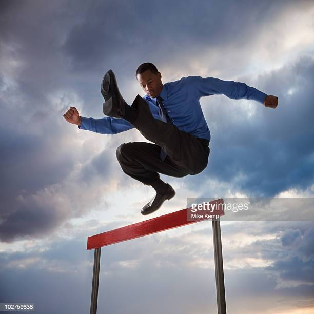 Businessman jumping over a hurdle
