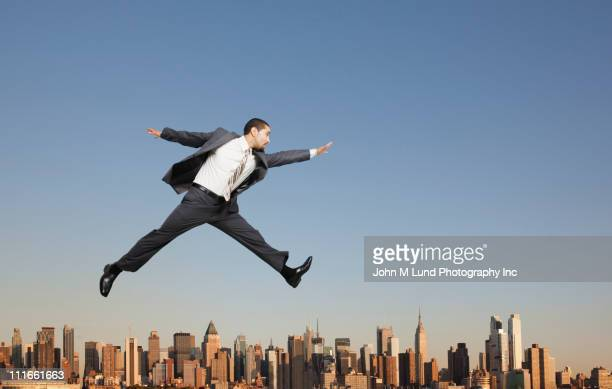 Businessman jumping over highrise buildings