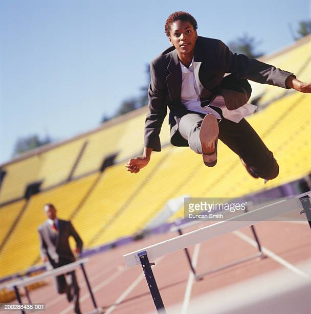 Businessman jumping over hurdles in stadium, low angle view