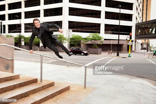 businessman jumping over railing at sidewalk in city - 背広 ストックフォトと画像