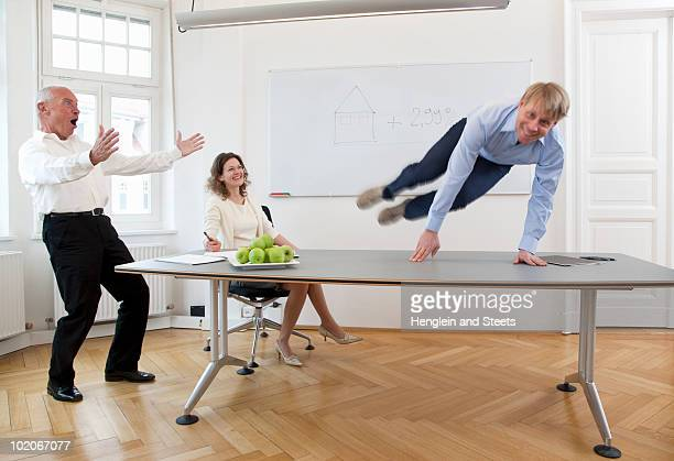 Businessman jumping over table