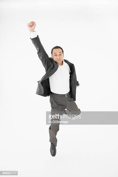 businessman jumping, raising fist, studio shot - ガッツポーズ ストックフォトと画像