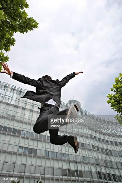 Businessman jumping, rear view