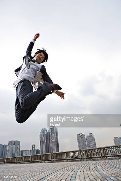 Businessman jumping, smiling