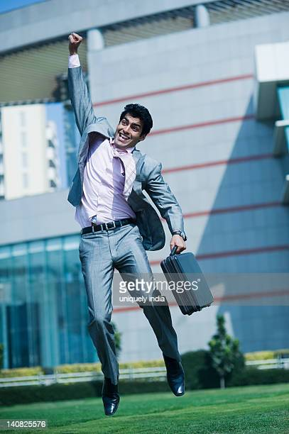 Businessman jumping up with a briefcase in hand, Gurgaon, Haryana, India