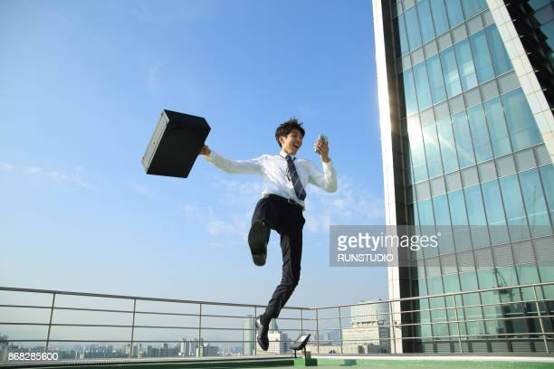 businessman jumping with briefcase - overhemd en stropdas stockfoto's en -beelden