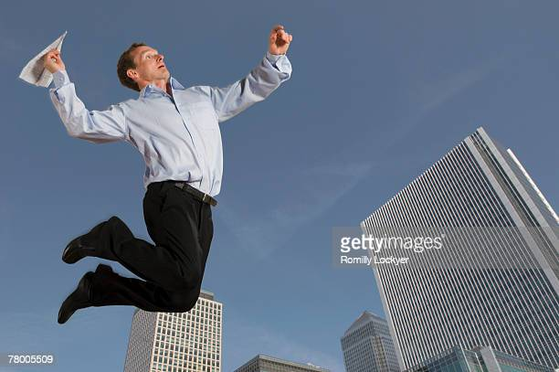 Businessman jumping with paper airplane