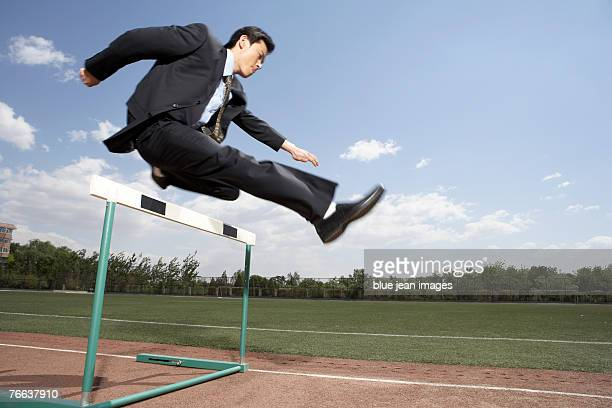 a businessman jumps a hurdle. - hurdling track event stock pictures, royalty-free photos & images
