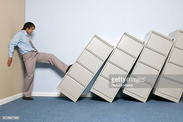 Businessman Kicking Over File Cabinets