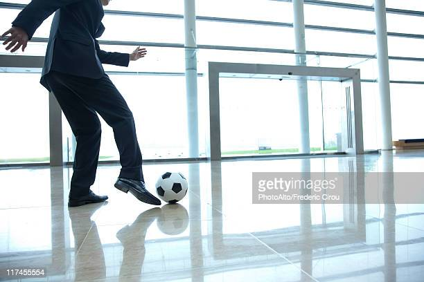 businessman kicking soccer ball in lobby - tirare in rete foto e immagini stock