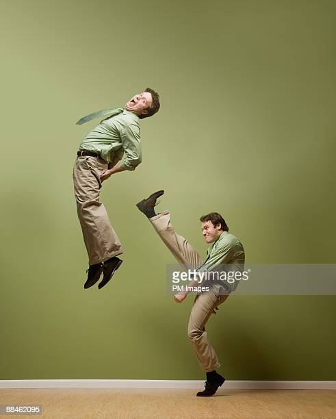 businessman kicks himself - buttock stock pictures, royalty-free photos & images