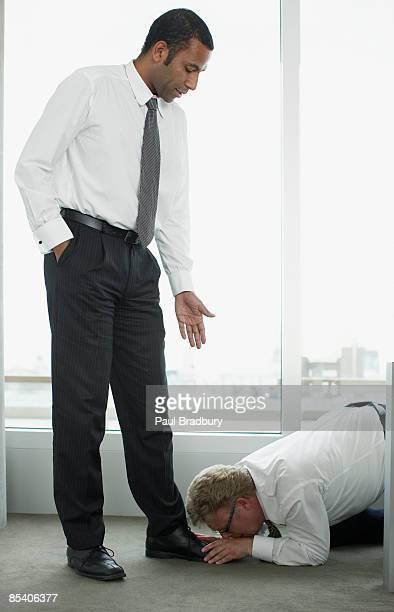 Businessman kissing boss feet