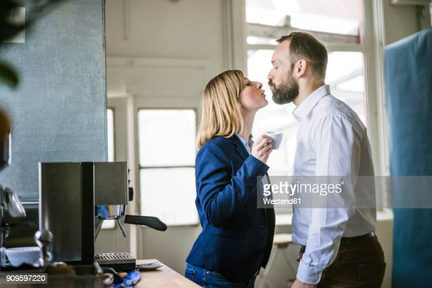 businessman kissing businesswoman in office - work romance stock pictures, royalty-free photos & images