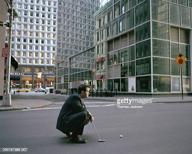 Businessman kneeling in street with putter, side view