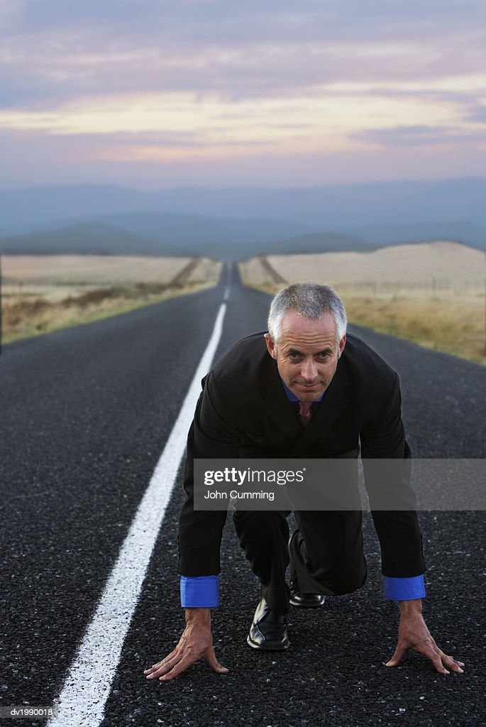 Businessman Kneeling on a Remote Road in Preparation for a Race : Stock Photo