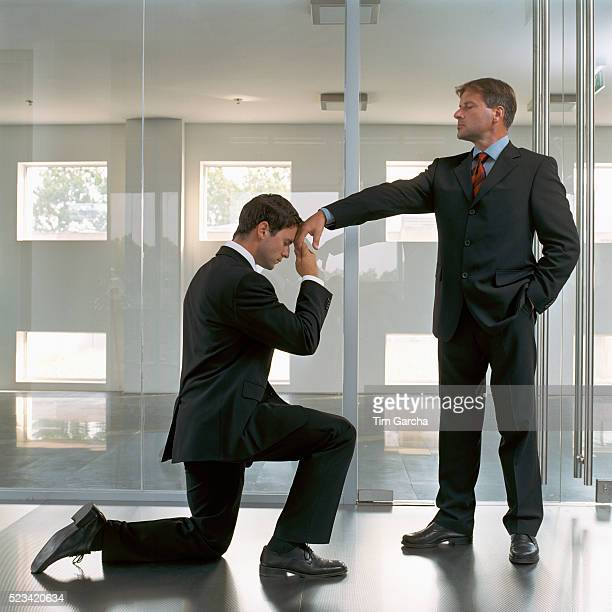 businessman kneeling to superior - humility stock pictures, royalty-free photos & images