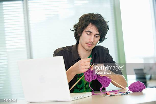 Businessman knitting in front of a laptop