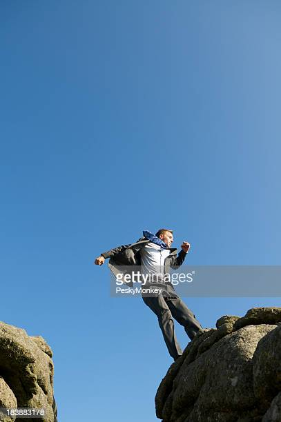 Businessman Lands at the Edge of a Rock Cliff