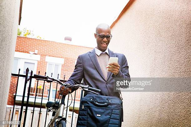 businessman laughing at mobile phone coming back home - black alley stock photos and pictures