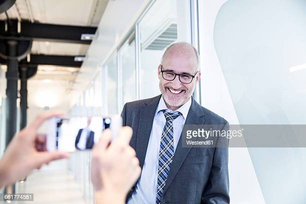 Businessman laughing while woman taking picture of him with smartphone