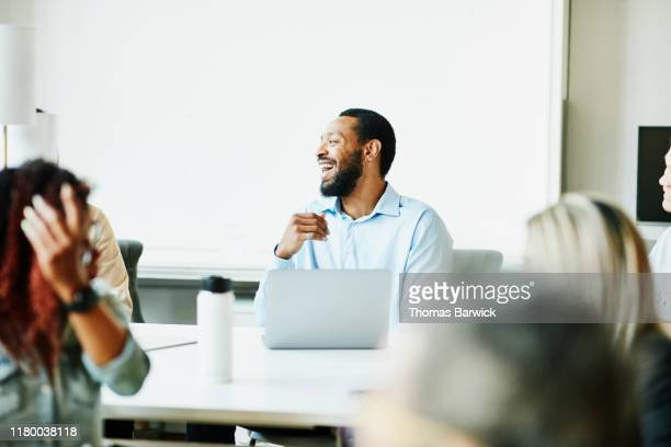 businessman laughing with colleagues while working together in coworking space - laughing stock pictures, royalty-free photos & images