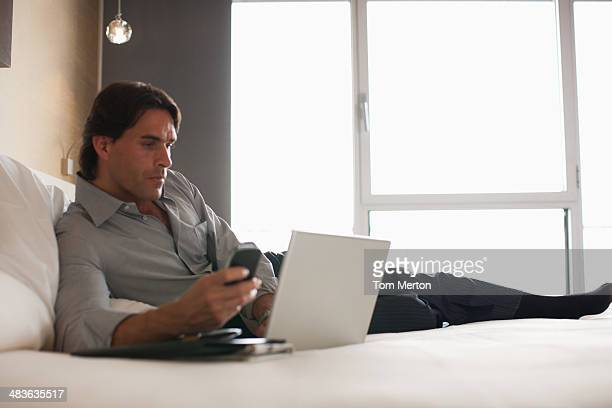 Businessman laying on bed using laptop in hotel room