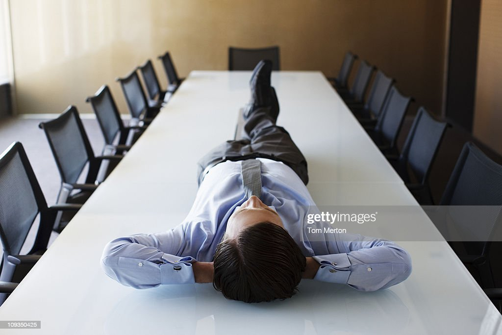 Businessman laying on conference room table : Stock Photo