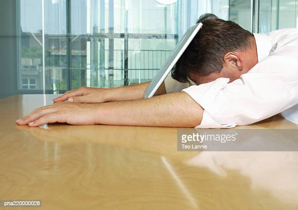 Businessman laying with face on laptop.