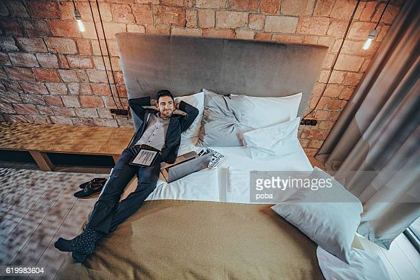 businessman laying with laptop on hotel bed