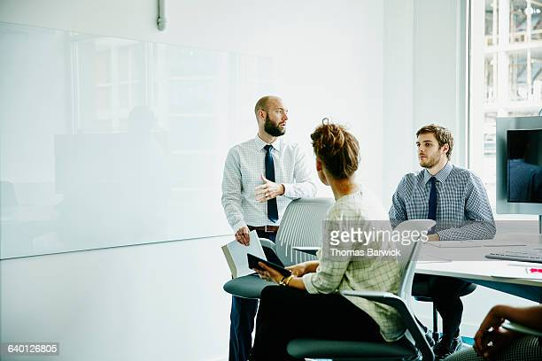 businessman leading discussion during meeting - tres personas fotografías e imágenes de stock
