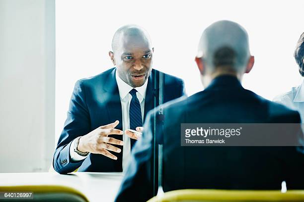 businessman leading discussion during meeting - black suit stock pictures, royalty-free photos & images