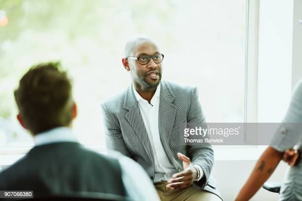 businessman leading team during informal team meeting in office - leadership stock pictures, royalty-free photos & images