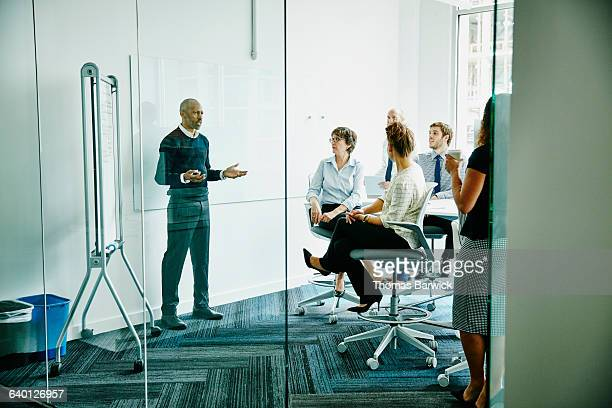 Businessman leading team meeting at whiteboard