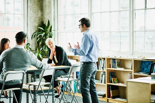 Businessman leading team meeting in design studio conference room - gettyimageskorea