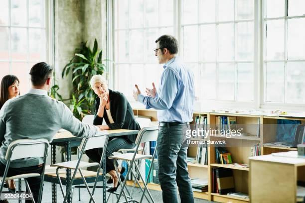 Businessman leading team meeting in design studio conference room
