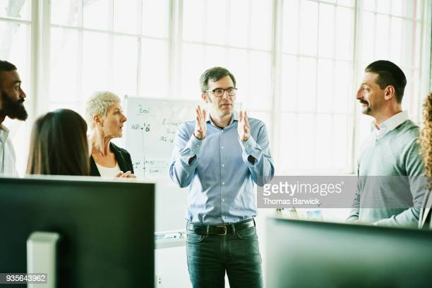 businessman leading team meeting in high tech start up office - guidance stock pictures, royalty-free photos & images