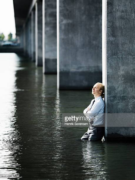 Businessman leaning against a pillar in water