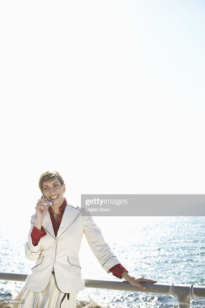 Businessman Leaning Against a Railing on a Waterfront and Using Her Mobile Phone : Stock Photo