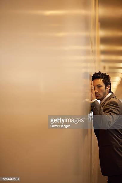businessman leaning against a wall - oliver eltinger stock-fotos und bilder